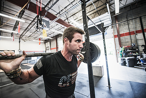 Young male crossfitter lifting bar bell on shoulders in gym